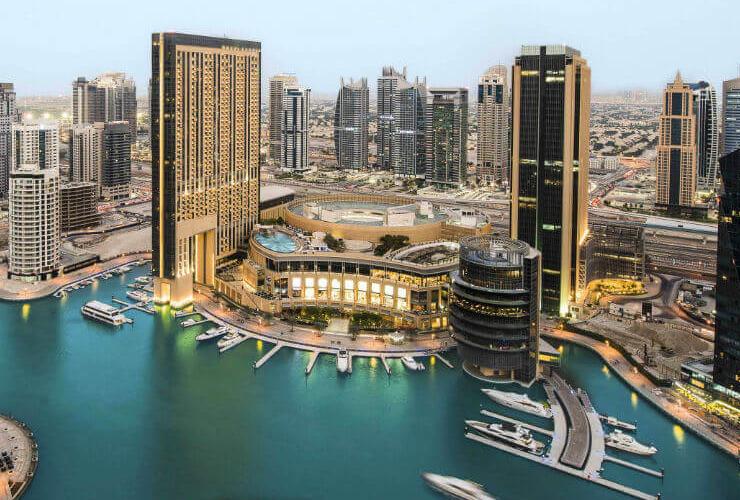 高層ビルに囲まれた港に建つホテル